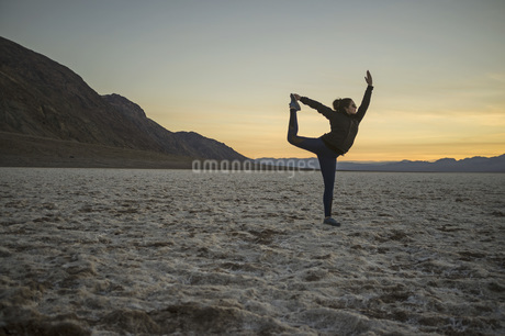 Full length of young woman doing yoga in desert at sunset, Death Valley, Nevada, USAの写真素材 [FYI04322871]