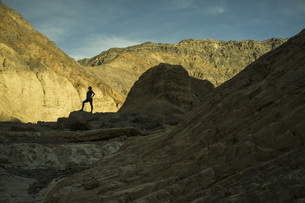 Silhouette of woman standing in rocky landscape, Death Valley, Nevada, USAの写真素材 [FYI04322872]
