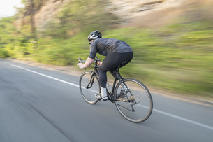 Blurred motion view of man cycling on country roadの写真素材 [FYI04322876]