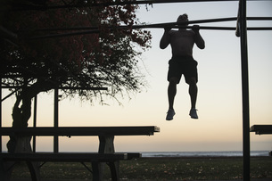 Full length of man doing chin-ups at park against sky at sunsetの写真素材 [FYI04322877]