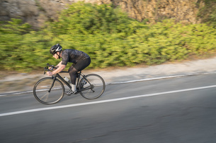 Side view of man cycling on country roadの写真素材 [FYI04322882]