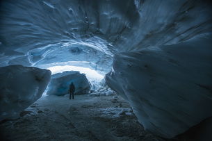 A man carrying snowboard while standing in ice cave, Whistler, British Columbia, Canadaの写真素材 [FYI04322887]