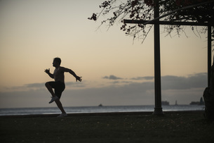 Full length of man jogging in park by sea at sunsetの写真素材 [FYI04322889]