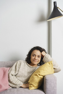 Portrait of smiling woman relaxing on sofa at homeの写真素材 [FYI04322998]