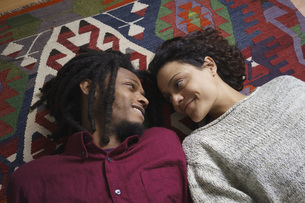 High angle view of affectionate couple looking at each other while lying on carpetの写真素材 [FYI04323000]