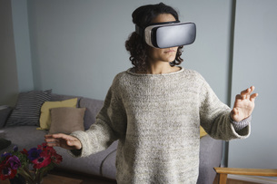 Woman using virtual reality headset while standing in living roomの写真素材 [FYI04323006]