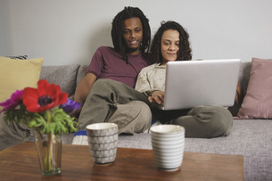 Young multi-ethnic couple using laptop while sitting on sofa at homeの写真素材 [FYI04323008]