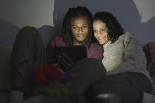 Smiling multi-ethnic couple using digital tablet in dark living roomの写真素材 [FYI04323010]