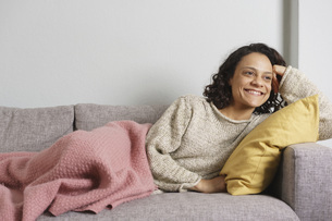Thoughtful woman smiling while relaxing on sofa at homeの写真素材 [FYI04323011]