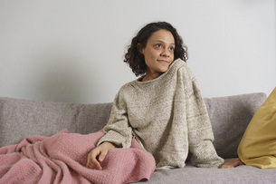 Thoughtful woman looking away while sitting on sofa at homeの写真素材 [FYI04323016]