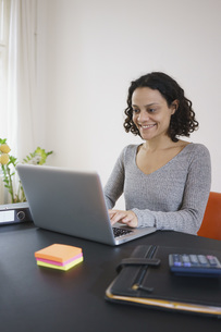 Happy woman using laptop at table in houseの写真素材 [FYI04323018]