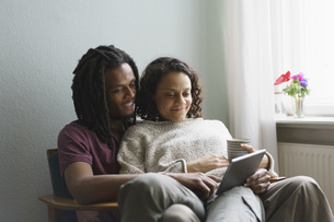Young multi-ethnic couple using digital tablet while sitting on armchair at homeの写真素材 [FYI04323019]