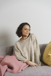 Thoughtful woman looking away while sitting on sofa against white wallの写真素材 [FYI04323020]
