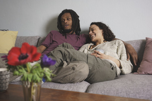 Cheerful multi-ethnic couple relaxing on sofa at homeの写真素材 [FYI04323023]