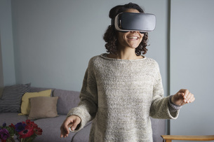 Happy woman using virtual reality headset while standing in living roomの写真素材 [FYI04323025]