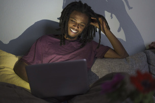 Happy man using laptop while sitting on sofa at homeの写真素材 [FYI04323027]