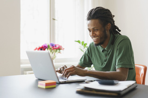 Happy man using laptop at table in houseの写真素材 [FYI04323028]