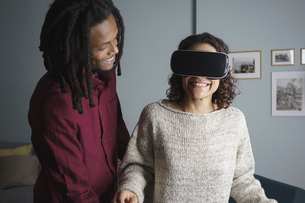 Happy man looking at woman using virtual reality headset in living roomの写真素材 [FYI04323029]