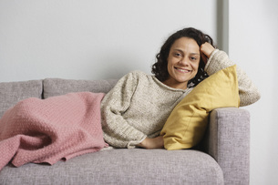 Portrait of happy woman relaxing on sofa at homeの写真素材 [FYI04323031]