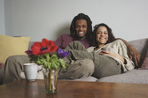 Portrait of happy multi-ethnic couple relaxing on sofa at homeの写真素材 [FYI04323036]