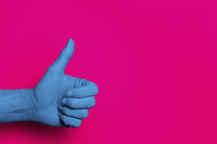 Close-up of blue painted hand showing thumb up against pink backgroundの写真素材 [FYI04323048]