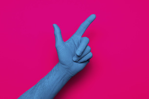 Close-up of blue painted hand pointing against pink backgroundの写真素材 [FYI04323054]