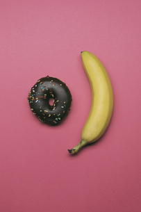 Directly above shot of donut and banana on pink backgroundの写真素材 [FYI04323056]