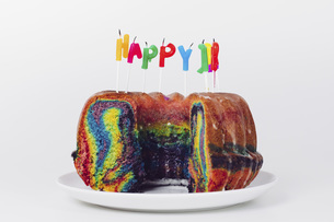 Close-up of birthday candles on rainbow cake in plate against white backgroundの写真素材 [FYI04323060]