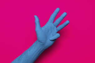 Close-up of blue painted hand gesturing against pink backgroundの写真素材 [FYI04323062]