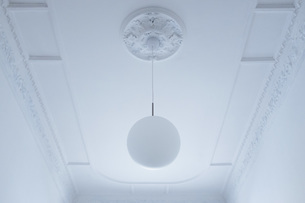 Low angle view of pendant light hanging from white ceiling at homeの写真素材 [FYI04323063]