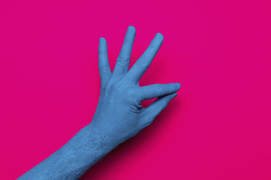Close-up of blue painted hand gesturing OK sign against pink backgroundの写真素材 [FYI04323064]