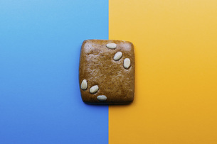 Directly above shot of cookie on blue and yellow backgroundの写真素材 [FYI04323065]