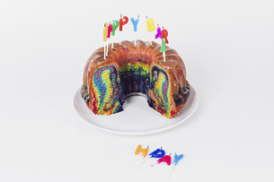Birthday candles on rainbow cake against white backgroundの写真素材 [FYI04323071]