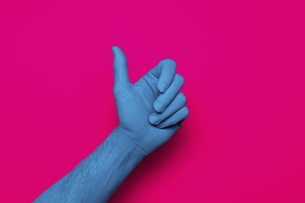 Close-up of blue painted hand gesturing thumb up against pink backgroundの写真素材 [FYI04323073]