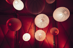 Low angle view of illuminated pendant lights hanging from ceilingの写真素材 [FYI04323075]