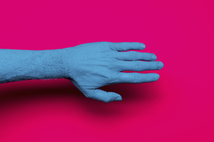Close-up of blue painted hand over pink backgroundの写真素材 [FYI04323079]