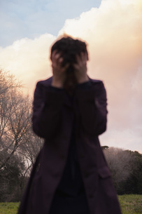 Depressed woman standing against sky during sunsetの写真素材 [FYI04323089]