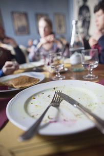 Fork and knife on plate with people sitting at dining table in backgroundの写真素材 [FYI04323093]