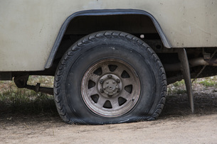 Close-up of vehicle with flat tire on fieldの写真素材 [FYI04323114]