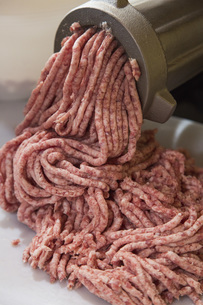 High angle view of meat being minced in factoryの写真素材 [FYI04323115]