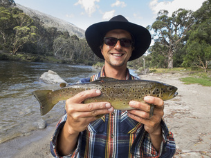 Portrait of happy mature man holding fish by river, Jindabyne, New South Wales, Australiaの写真素材 [FYI04323121]