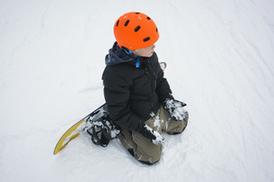 High angle view of boy with snowboard kneeling in snowの写真素材 [FYI04323138]