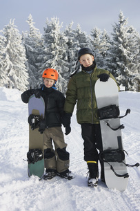 Full length portrait of brothers with snowboards standing on snow against treesの写真素材 [FYI04323141]