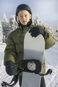 Portrait of boy in ski gear holding snowboardの写真素材 [FYI04323152]