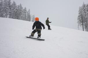 Boys snowboarding on slopesの写真素材 [FYI04323153]