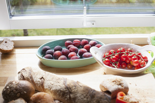 Close-up of fruits and bread on table by windowの写真素材 [FYI04323187]