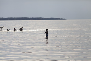 Children playing with ball in sea against clear skyの写真素材 [FYI04323195]