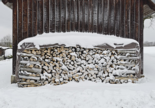 Stack of firewood outside house on snowy fieldの写真素材 [FYI04323203]
