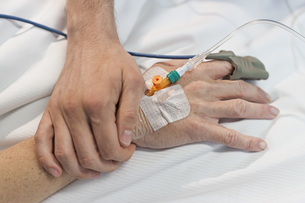 Close-up of man holding hand of a woman with IV drip at hospitalの写真素材 [FYI04323221]
