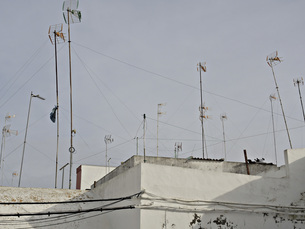Low angle view of television aerials on building against clear skyの写真素材 [FYI04323292]